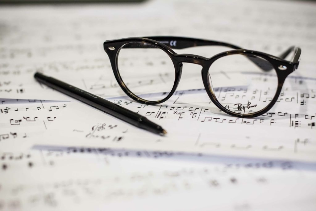 Pages of musical score with pen and glasses
