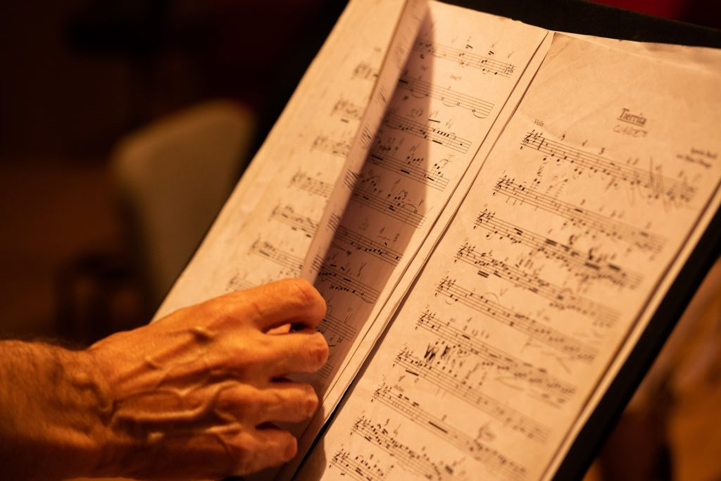 Hand turning page of music while studying a score
